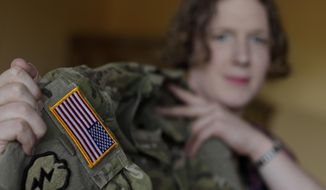 In this July 29, 2017, file photo, transgender U.S. Army Capt. Jennifer Sims lifts her uniform during an interview with The Associated Press in Beratzhausen near Regensburg, Germany. (AP Photo/Matthias Schrader) ** FILE **