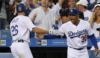 Los Angeles Dodgers' Chase Utley, left, is congratulated by manager Dave Roberts after scoring on a single by Yasiel Puig during the ninth inning of a baseball game against the San Francisco Giants, Sunday, July 30, 2017, in Los Angeles. (AP Photo/Mark J. Terrill)