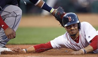 Boston Red Sox's Mookie Betts, right, beats a pick-off tag by Cleveland Indians first baseman Carlos Santana as he dives back safely to first during the second inning of a baseball game at Fenway Park, Monday, July 31, 2017, in Boston. (AP Photo/Charles Krupa)