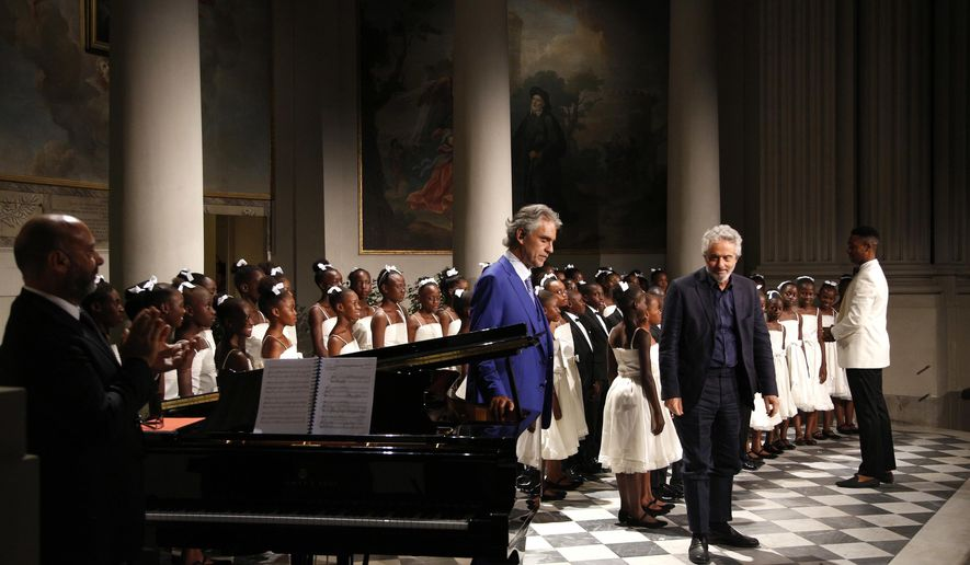 """Tenor Andrea Bocelli, center left, and composer Nicola Piovani, center right, acknowledge applause as they perform with the """"Voices of Haiti"""" children's choir during the gala concert that inaugurates the Franco Zeffirelli International Center For Performing Arts, in Florence, Italy, Monday, July 31, 2017. The center, besides its educational activities, brings together the entire artistic and cultural patrimony of the Italian director's almost 70-year career, including over ten thousand books from his personal library, thousands of professional documents and notes, designs, sketches, scripts, screenplays and storyboards, as well as a substantial collection of photographs of his works from the post-war years to present days. (AP Photo/Domenico Stinellis)"""