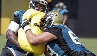 Jacksonville Jaguars offensive linemen Branden Albert, left, and Tyler Shatley, right, perform a drill during NFL football training camp, Friday, July 28, 2017, in Jacksonville, Fla. (AP Photo/John Raoux)