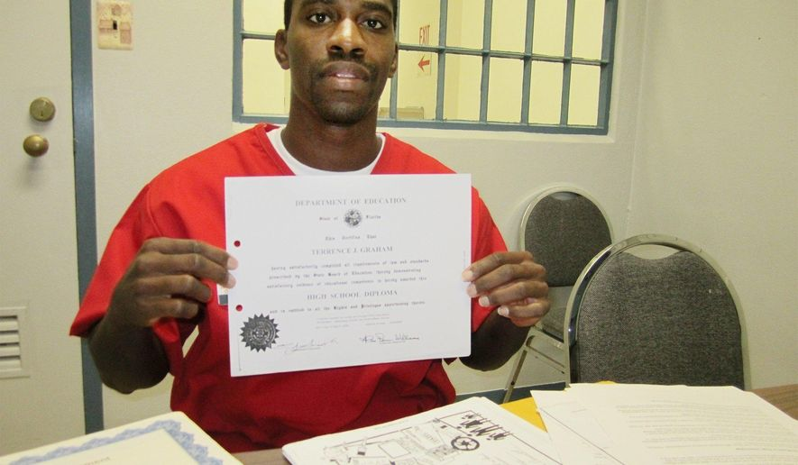 In this December 2016 photo, Terrance Graham holds the high school diploma he earned while he was incarcerated in Florida State Prison at Raiford, Fla. At 16, Graham had been ordered to spend the rest of his life behind bars for a 2004 armed home invasion. Graham was on probation at the time after participating in an attempted restaurant robbery a year earlier. Graham had no option for freedom other than executive clemency. But the Supreme Court ruled that life without parole for a crime that doesn't involve murder is unconstitutional. Graham was ultimately resentenced to 25 years in prison, making him eligible to leave jail by 2026. (Tessa Duvall/The Florida Times-Union via AP)