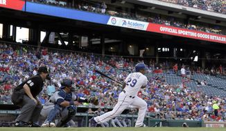 Home plate umpire Doug Eddings and Seattle Mariners catcher Carlos Ruiz watch as Texas Rangers' Adrian Beltre follows through on a single to center off a pitch from Mariners starter Felix Hernandez in the first inning of a baseball game, Monday, July 31, 2017, in Arlington, Texas. (AP Photo/Tony Gutierrez)