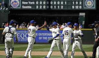 Seattle Mariners' Leonys Martin, center right, and Hansel Robles (47) high-five after they defeated the New York Mets in a baseball game, Sunday, July 30, 2017, in Seattle. (AP Photo/Ted S. Warren)