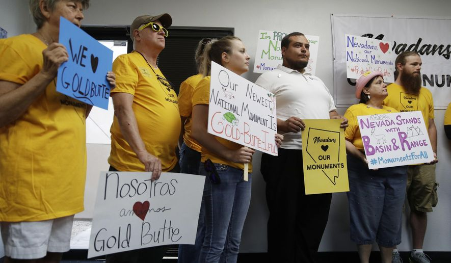 People hold up signs during a news conference by supporters of the Basin and Range and Gold Butte National Monuments, Monday, July 31, 2017, in Las Vegas. The supporters held the news conference after Interior Secretary Ryan Zinke cancelled a meeting with Gold Butte advocates scheduled for Monday. (AP Photo/John Locher)