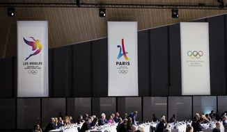 FILE - This July 11, 2017 file photo shows banners of Los Angeles 2024 candidacy, Paris 2024 candidacy and the International Olympic Committee (IOC), during the International Olympic Committee (IOC) Extraordinary Session, at the SwissTech Convention Centre, in Lausanne, Switzerland. It was announced Monday, July 31, that Los Angeles has reached an agreement with international Olympic leaders that will open the way for the city to host the 2028 Summer Games, while ceding the 2024 Games to rival Paris. (Jean-Christophe Bott/Keystone via AP,File)