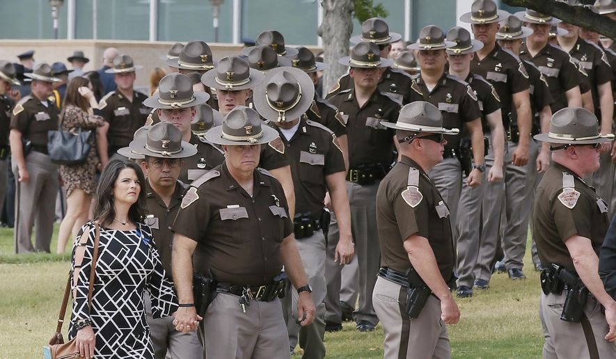Oklahoma Highway Patrol troopers and their families line up to enter the funeral of Lt. D. Heath Meyer in Norman, Okla., Monday, July 31, 2017. Meyer was struck by another trooper's patrol car during a chase July 14, 2017, and died July 24, 2017. (AP Photo/Sue Ogrocki)