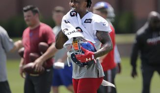 FILE - In this June 13, 2017, file photo, New York Giants' Brandon Marshall wipes away sweat during NFL football practice in East Rutherford, N.J. Marshall said it takes the entire offense working in sync to pull off the fake properly, from the running back going full speed as if he's getting the ball to the quarterback hiding the ball. Marshall said former teammate Peyton Manning was the best he's seen at that. (AP Photo/Seth Wenig, File)