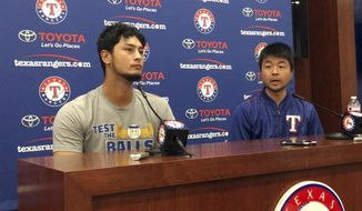 Former Texas Rangers pitcher Yu Darvish, left, responds to a question with help from his translator Hideaki Sato during a news conference regarding his trade to the Los Angeles Dodgers before a baseball game against the Seattle Mariners on Monday, July 31, 2017, in Arlington, Texas. (AP Photo/Tony Gutierrez)