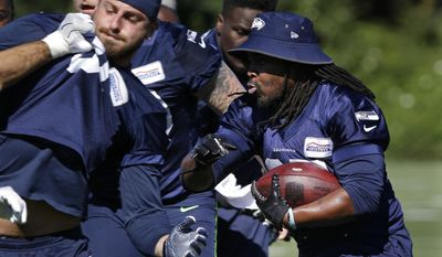 Seattle Seahawks running back Eddie Lacy, right, carries the ball during an NFL football training camp, Monday, July 31, 2017, in Renton, Wash. (AP Photo/Ted S. Warren)