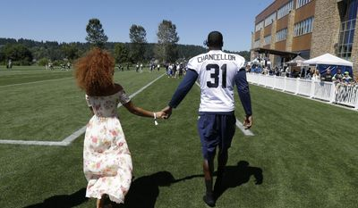 Seattle Seahawks strong safety Kam Chancellor holds hands with his wife Tiffany after NFL football training camp, Monday, July 31, 2017, in Renton, Wash. (AP Photo/Ted S. Warren)