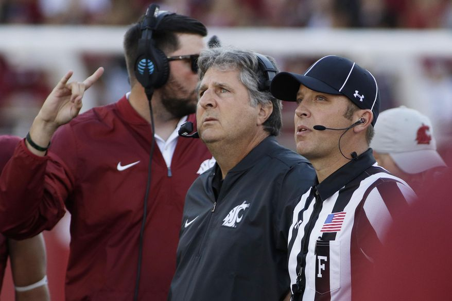FILE - In this Sept. 3, 2016, file photo, Washington State head coach Mike Leach, center, watches a replay during the first half of an NCAA college football game against the Eastern Washington, in Pullman, Wash. To keep fans in the stands and those watching on TV or mobile devices engaged, the NFL, NBA and Major League Baseball have taken steps to shorten games. Now it's college football's turn. (AP Photo/Young Kwak, File)