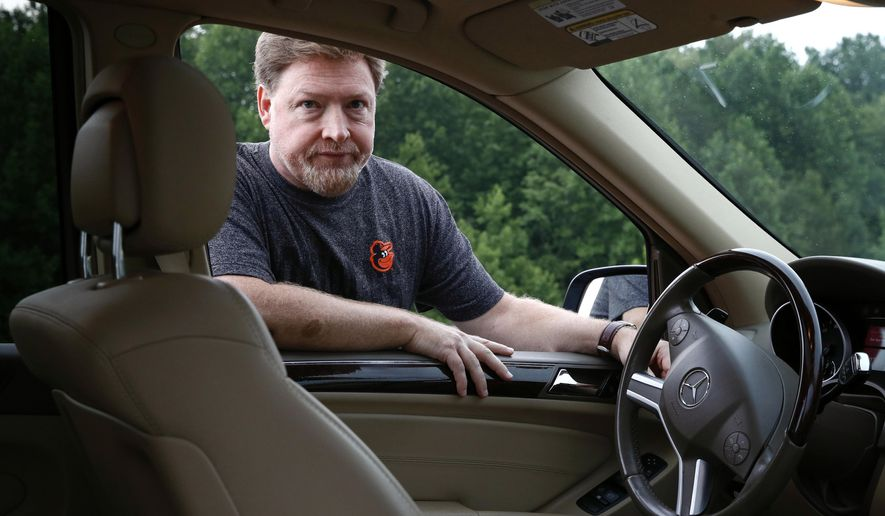 In this July 28, 2017, photo, John Carroll poses alongside his 2010 Mercedes-Benz ML 350 sport utility vehicle, which contains a driver's side Takata air bag inflator that has been recalled, in Perry Hall, Md. Carroll is waiting for parts in order for his recalled inflator to be replaced. A government effort to speed up recalls of more than 21 million of the most dangerous Takata air bag inflators is falling short, according to an analysis of completion rates by The Associated Press. (AP Photo/Patrick Semansky)