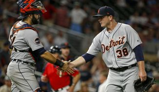 FILE - In this July 21, 2017, file photo, Detroit Tigers catcher Alex Avila and relief pitcher Justin Wilson celebrate the team's 6-3 win over the Minnesota Twins,  in a baseball game in Minneapolis. The rolling Chicago Cubs got a big lift Monday, July 31, 2017, when they acquired reliever Justin Wilson and catcher Alex Avila in a trade with the Detroit Tigers, bolstering their chance for another long playoff run. (AP Photo/Bruce Kluckhohn, File)