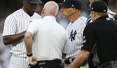 New York Yankees trainer Steve Dohonue, second from left, and manager Joe Giradi, third from left, check on New York Yankees starting pitcher Luis Severino, far right, after Severino loaded the bases during the first inning of a baseball game against the Detroit Tigers at Yankee Stadium in New York, Monday, July 31, 2017. Home plate umpire Marvin Hudson is at far right, and New York Yankees catcher Gary Sanchez joins the group. (AP Photo/Kathy Willens)