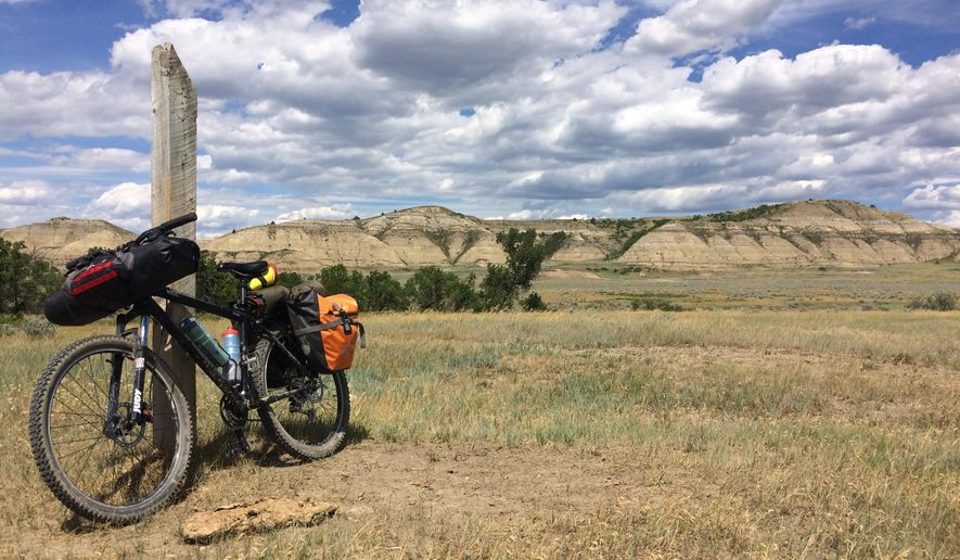 This June 19, 2017 photo shows a fully loaded hardtail mountain bike propped up by a trail-marking post on the Maah Daah Hey Trail near Medora, North Dakota. The wooden fence posts placed along the trail were within sight of each other for easy navigation. (AP Photo/Carey J. Williams)