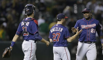 Minnesota Twins pitcher Brandon Kintzler (27) celebrates the team's 6-3 win over the Oakland Athletics with catcher Jason Castro, left, and Miguel Sano (22), following a baseball game Friday, July 28, 2017, in Oakland, Calif. (AP Photo/Ben Margot)