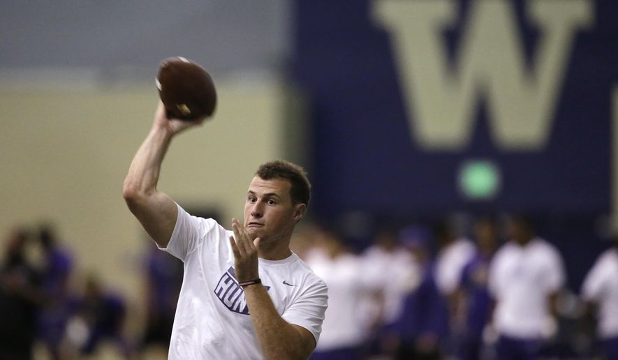 Washington quarterback K.J. Carta-Samuels throws at the team's first official NCAA college football practice of the year Monday, July 31, 2017, in Seattle. (AP Photo/Elaine Thompson)