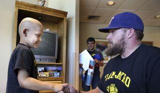 In this photo made Saturday, April 7, 2017, Cancer patient Jayro Ponce, 9, left, meets New York Giants center Weston Richburg at the Harrington Cancer Center in Amarillo, Texas. (Lauren Koski/Amarillo Globe-News via AP)