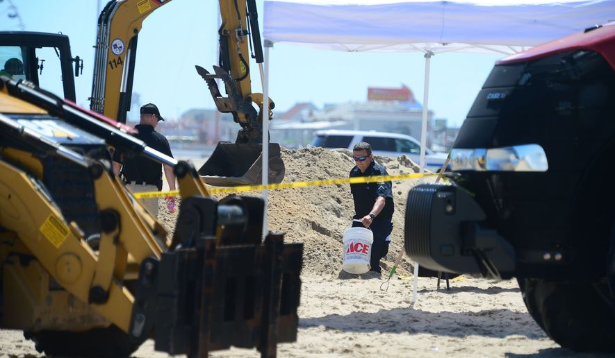 In this Monday, July 31, 2017, photo, Ocean City Police carry out buckets of sand to be sifted from a deep hole that was dug around the area where a body was found in Ocean City, Md. Police say the body of Ashley O'Connor, a 30-year-old Texas woman, was found buried on the beach with just an arm above the sand. (Megan Raymond/The Daily Times via AP)