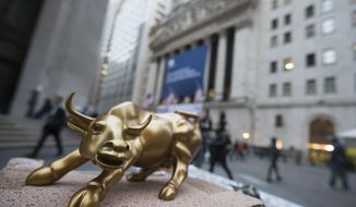 "FILE - In this Tuesday, Oct. 25, 2016, file photo, a miniature reproduction of Arturo Di Modica's ""Charging Bull"" sculpture sits on display at a street vendor's table outside the New York Stock Exchange, in lower Manhattan. U.S. Stocks are rising Tuesday, Aug. 1, 2017, as payment processors and banks trade higher. (AP Photo/Mary Altaffer, File)"