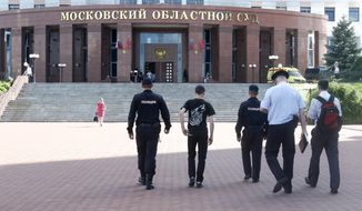 Police officers walk towards to the main entrance of Moscow Regional Court is seen in Moscow, Russia, Tuesday, Aug. 1, 2017. Five defendants at the Moscow courthouse attacked their guards in a bungled escape attempt, leading to a shootout that killed a few people and wounded five others, officials said Tuesday. (Andrey Nikerichev/Moscow News Agency via AP)