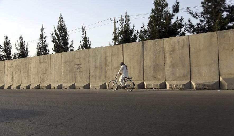 In this Monday, July 31, 2017 photo, an Afghan man ride his bicycle walks past blast walls in Kabul, Afghanistan. A U.S. watchdog says unprecedented security restrictions are making it difficult to monitor Afghanistan projects that are costing hundreds of millions of U.S. tax dollars. (AP Photos/Rahmat Gul)