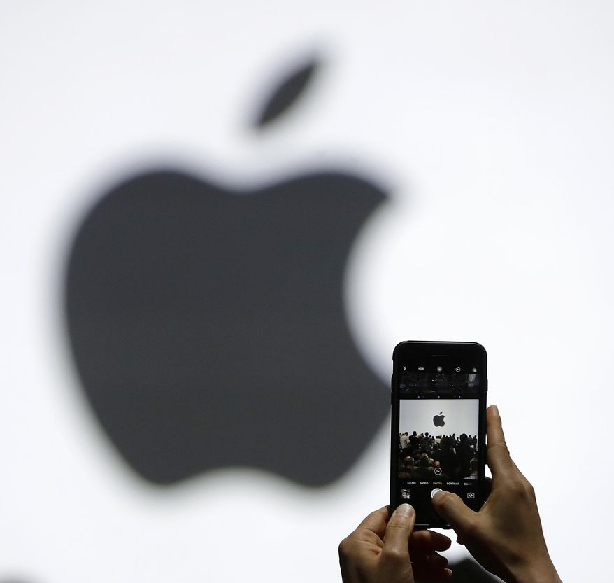 In this Monday, June 5, 2017, file photo, a person takes a photo of an Apple logo before an announcement of new products at the Apple Worldwide Developers Conference in San Jose, Calif. Apple is getting ready to use iPhone cameras as an entryway into the strange world of augmented reality, taking the trend-setting company down an avenue that could usher in a new era in technology. (AP Photo/Marcio Jose Sanchez, File)