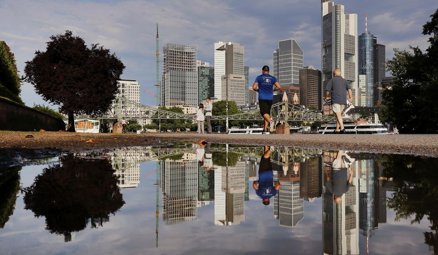 The skyline of the banking district is reflected in a puddle after a heavy thunderstorm during the night in Frankfurt, Germany, Tuesday, Aug. 1, 2017. (AP Photo/Michael Probst)