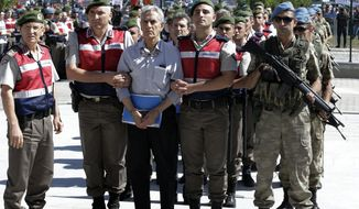 Paramilitary police and members of the special forces escort former Air Force Cmdr. Akin Ozturk and other suspects of last year's failed coup, outside the courthouse at the start of a trial, in Ankara, Turkey, Tuesday, Aug. 1, 2017.  Nearly 500 suspects, including a number of generals and military pilots, went on trial in Turkey Tuesday, accused of leading last year's failed coup attempt and carrying out attacks from an air base in Ankara. (AP Photo/Burhan Ozbilici)