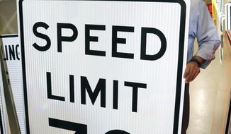 Arkansas Department of Transportation spokesman Danny Straessle props up a 70 mph sign inside the agency's sign shop in Little Rock on Tuesday, Aug. 1, 2017. Legislators authorized 75 mph speed limits under a state law that took effect Tuesday, but highway officials say engineers must study road designs and traffic patterns before allowing speeds above 70 mph. (AP Photo/Kelly P. Kissel)