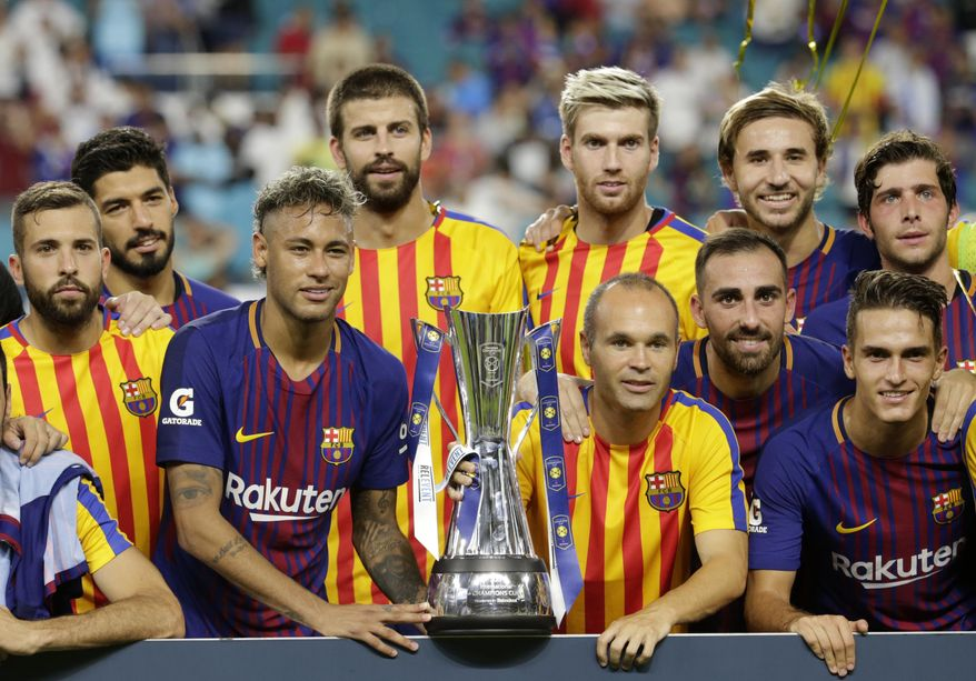 Barcelona's Neymar, second from left front, and teammates pose with the trophy after defeating Real Madrid in an International Champions Cup soccer match, Saturday, July 29, 2017, in Miami Gardens, Fla. (AP Photo/Lynne Sladky)