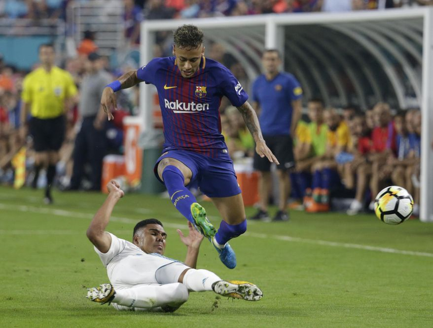 Real Madrid's Casemiro, left, falls to the field as he vies for the ball with Barcelona's Neymar, right, during the first half of an International Champions Cup soccer match, Saturday, July 29, 2017, in Miami Gardens, Fla. (AP Photo/Lynne Sladky)