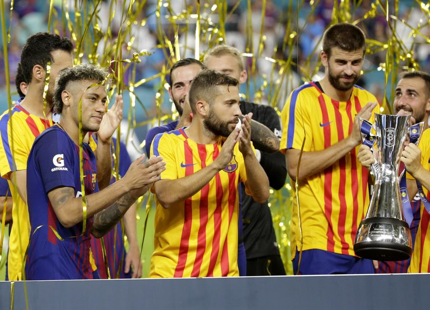 Barcelona's Neymar, left, and his teammates stand with the trophy after defeating Real Madrid 3-2 in an International Champions Cup soccer match, Saturday, July 29, 2017, in Miami Gardens, Fla. (AP Photo/Lynne Sladky)