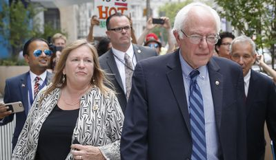 In this July 28, 2016 file photo, Sen. Bernie Sanders, I-Vt. and his wife Jane walk through downtown in Philadelphia during the final day of the Democratic National Convention. An economic development official says a financial services company had considering buying some of a now-defunct college's lakefront property while Jane Sanders was president of the school. Burlington College closed last year after struggling under the weight of its $10 million purchase of property and buildings from the Roman Catholic Diocese of Burlington in 2010 during Jane Sanders' presidency. (AP Photo/John Minchillo, File)