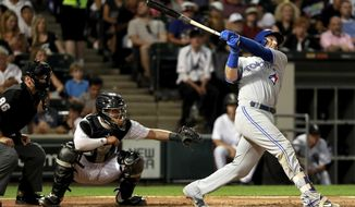 Toronto Blue Jays' Justin Smoak watches his two-run home run in front of Chicago White Sox catcher Omar Narvaez, center, and umpire David Rackley during the fifth inning of a baseball game in Chicago, Tuesday, Aug. 1, 2017. (AP Photo/Jeff Haynes)