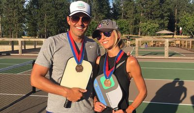 In this July 21, 2017 photo provided by Giuliana Rancic, Bill and Giuliana Rancic pose for a photo in Harrison, Idaho after winning a Mixed Doubles Pickleball Tournament. It's tempting to blow off a workout, but getting sweaty with your significant other makes a workout more fun and ups the intensity ante. (Giuliana Rancic via AP)