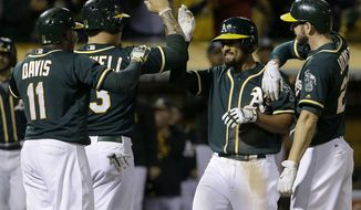 Oakland Athletics' Marcus Semien, second from right, celebrates after hitting a grand slam home run that scored Rajai Davis, from left, Bruce Maxwell, and Matt Joyce during the sixth inning of a baseball game against the San Francisco Giants in Oakland, Calif., Monday, July 31, 2017. (AP Photo/Jeff Chiu)