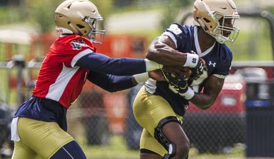 Notre Dame quarterback Brandon Wimbush, left, hands the ball off to running back Josh Adams during the first practice of fall camp for the NCAA college football team Tuesday, Aug. 1, 2017, in Culver, Ind. (Robert Franklin/South Bend Tribune via AP)