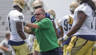 Notre Dame coach Brian Kelly, center, works with cornerback Donte Vaughn during the first day of fall camp for the NCAA college football game Tuesday, Aug. 1, 2017, in Culver, Ind. (Robert Franklin/South Bend Tribune via AP)