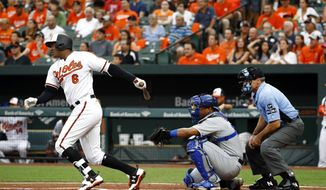 Baltimore Orioles' Jonathan Schoop, left, singles in front of Kansas City Royals catcher Salvador Perez and home plate umpire Angel Hernandez in the first inning of a baseball game in Baltimore, Tuesday, Aug. 1, 2017. Manny Machado scored on the play. (AP Photo/Patrick Semansky)