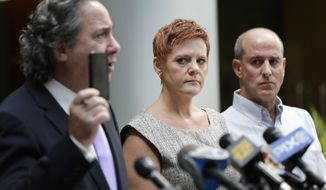 Dianne, center, and Seth Grossman, right, parents of Mallory Grossman, look as their attorney, Bruce Nagel, holds up a cell phone during a news conference in Roseland, N.J., Tuesday, Aug. 1, 2017. The New Jersey mother is suing her late daughter's school district because she says they didn't do enough to stop cyber bullying against her daughter that led the 12-year-old to kill herself. (AP Photo/Seth Wenig)