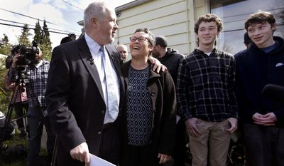 FILE - In this April 17, 2017, file photo, former Seattle Mayor Mike McGinn, front left, embraces his wife Peg Lynch as their sons Jack, right, and Cian McGinn look on before speaking to reporters in front of his home in Seattle. The top two candidates from a crowded field will emerge from the mayoral primary election, Tuesday, Aug. 1, 2017. McGinn is among those running. (AP Photo/Elaine Thompson, File)