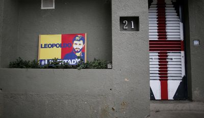 A banner with the image of opposition leader Leopoldo Lopez sits outside of his home in Caracas, Venezuela. Allies of two Venezuelan opposition leaders say Mr. Lopez and Antonio Ledezma were taken by authorities from the homes where they were under house arrest. (Associated Press)