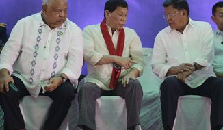 Philippine President Rodrigo Duterte, center, looks at the watch of Bureau of Internal Revenue Commissioner Caesar R. Dulay, right, as Executive Secretary Salvador Medialdea watch them during the 113th Founding Anniversary of the Bureau of Internal Revenue in metropolitan Manila, Wednesday, Aug. 2, 2017. The tough-talking Duterte briefly lashed out at North Korean leader Kim Jong Un in a speech before local revenue collectors Wednesday. (AP Photo/Aaron Favila)