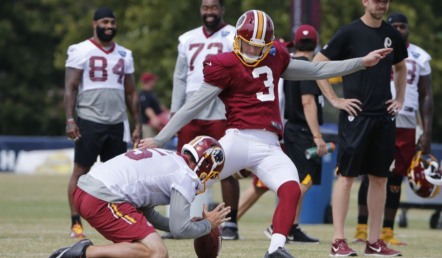 Washington Redskins kicker Dustin Hopkins (3) kicks the ball held by Tress Way, left, during practice at the Washington Redskins NFL training camp in Richmond, Va., Wednesday, Aug. 2, 2017. (AP Photo/Steve Helber)