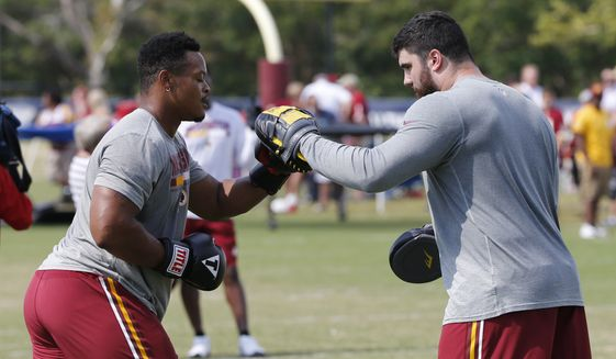 Washington Redskins defensive end Brandon Banks, left, and defensive tackle Matthew Ioannidis, right, practice their boxing moves during practice at the team's NFL training camp in Richmond, Va., Wednesday, Aug. 2, 2017. (AP Photo/Steve Helber)