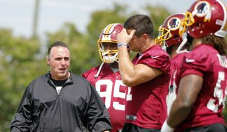 Washington Redskin defensive line coach, Jim Tomsula, left, talks with his players during practice at the Washington Redskins NFL training camp in Richmond, Va., Wednesday, Aug. 2, 2017. (AP Photo/Steve Helber)