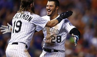Colorado Rockies' Charlie Blackmon, left, hugs Nolan Arenado after Arenado's single drove in Blackmon with the winning run, off New York Mets relief pitcher Hansel Robles during the ninth inning of a baseball game Tuesday, Aug. 1, 2017, Denver. The Rockies won 5-4. (AP Photo/David Zalubowski)