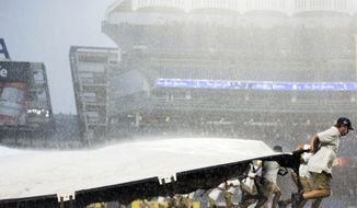 Field crews roll out the tarp due to inclement weather as the New York Yankees take on the Detroit Tigers in a baseball game on Wednesday, Aug. 2, 2017, in New York. (AP Photo/Michael Noble Jr.)e